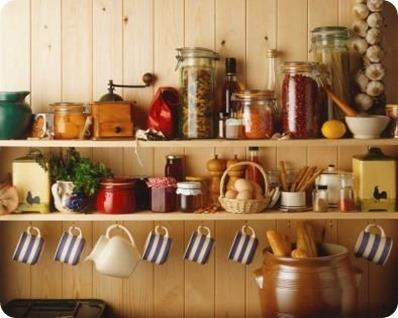 Dresser, shelves holding, jug, pickled produce, grinder, pasta in jar, lentils, salt and pepper pots, cups hanging from hooks, bread in jar, front view.