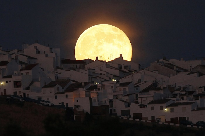 The Supermoon rises over houses in Olvera, in the southern Spanish province of Cadiz, July 12, 2014. Occurring when a full moon or new moon coincides with the closest approach the moon makes to the Earth, the Supermoon results in a larger-than-usual appearance of the lunar disk. REUTERS/Jon Nazca (SPAIN - Tags: SOCIETY CITYSCAPE TPX IMAGES OF THE DAY) ORG XMIT: JN657