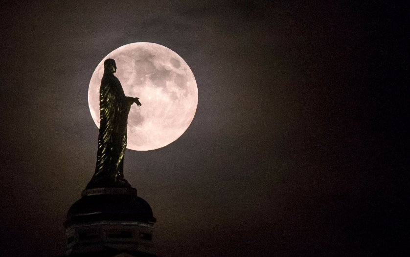 The full moon silhouettes the statue of the Virgin Mary on top the University of Notre Dame's golden dome on Monday, Sept. 8, 2014, in South Bend, Ind. (AP Photo/South Bend Tribune, Robert Franklin)